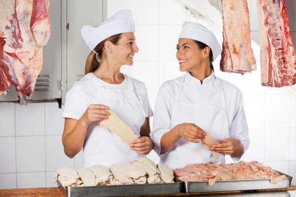 Happy female butchers holding raw meat at counter in shop