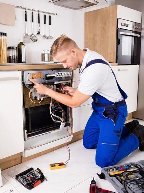 Un éléctricien en salopette blue répare une cuisinière dans une cuisine: