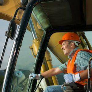 Un homme conduite une machine à chantier.