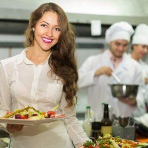 Une femme souriante tiens un plateau avec le répas dans sa main.