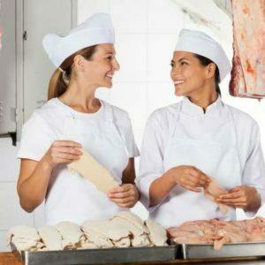 Deux ouvriers d'abattoir tenant de la viande crue au comptoir