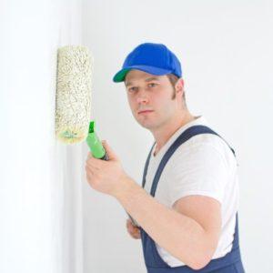 Un peintre peint les murs en blanc.
