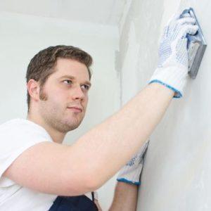 Un homme plâtrier plâtre le mur