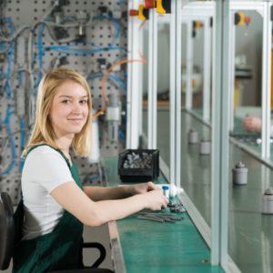Opérateure de production assise dans une usine.