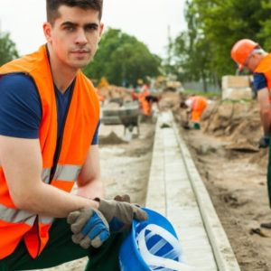 Le travailleur sur le chantier d'une construction routiere.