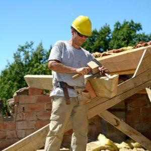Un charpente travaille sur une construction de toit