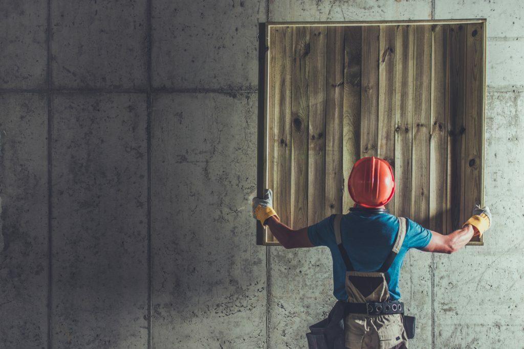 Travailleur de chantier de construction soulevant un élément en bois dans les airs. Intérieur en béton brut.