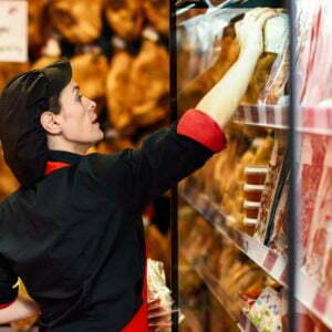 Une famme boucher dans une boucherie qui prend des produits des vitrines.